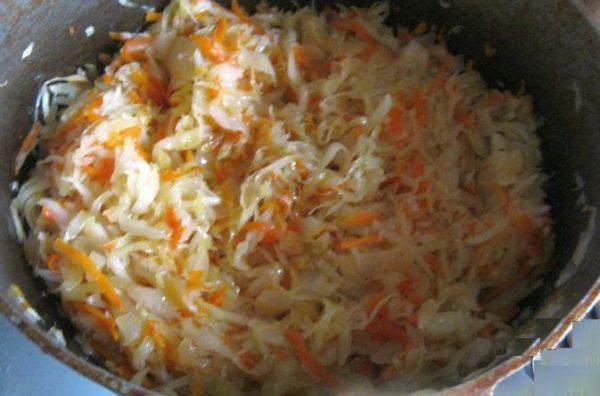 Добавьте к ним кислую капусту, закройте крышкой и тушите, периодически помешивая и подливая кислый капустный сок, столько же, сколько варятся ребрышки.
