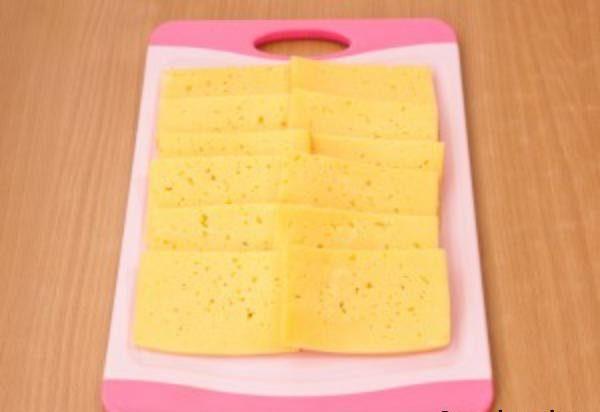 Нарезанный пластинками сыр разместите на разделочной доске.