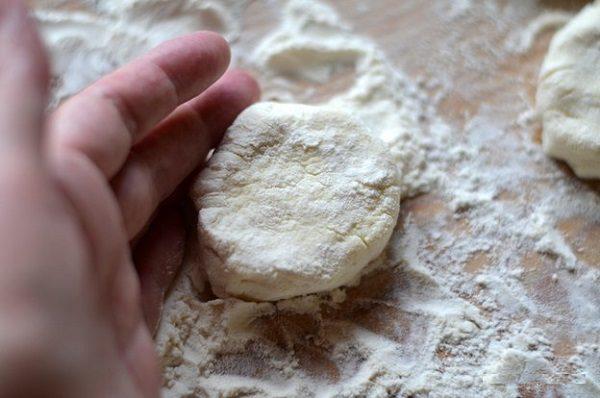 Каждый шарик будущего сырника выкладываем на присыпанную второй половиной муки доску и приплющиваем ладонью или ножом. Переворачиваем и снова слегка приплющиваем.