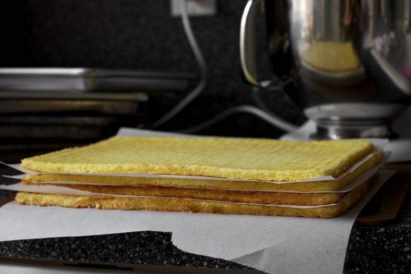 Каждый готовый корж аккуратно переворачивайте на решетку и прокладывайте пергаментом.