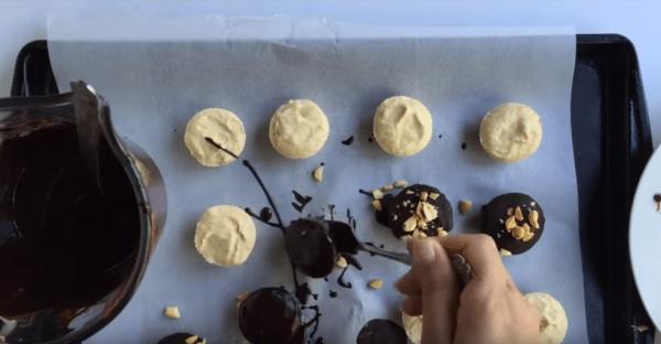 Растопите шоколад в микроволновке 30-40 секунд. Перемешайте. Каждую заготовку при помощи вилки обмакните в глазурь, одновременно посыпая орехом.